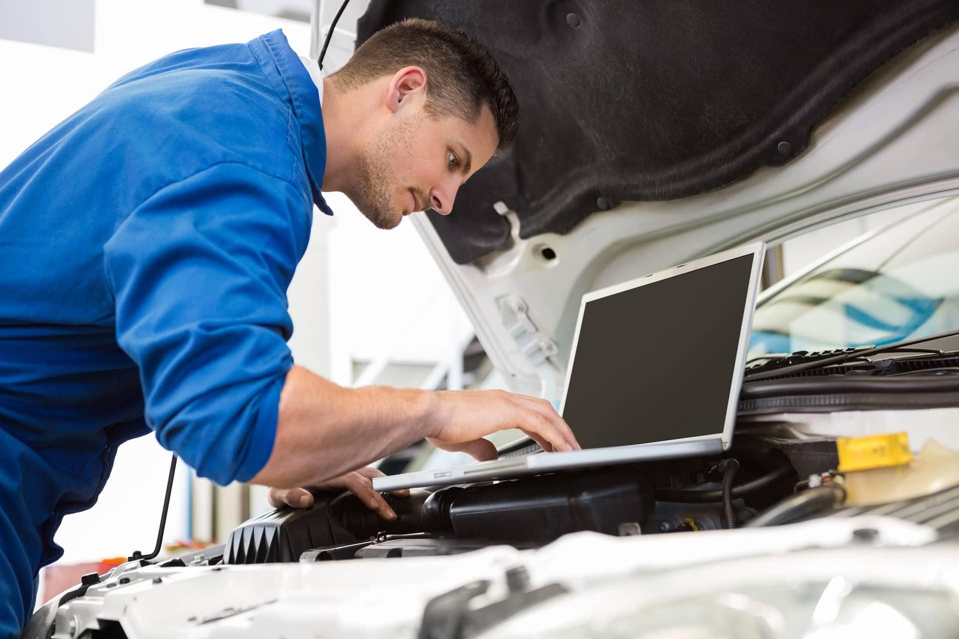 Ein Mechaniker nutzt seinen Laptop zur Datenauswertung.