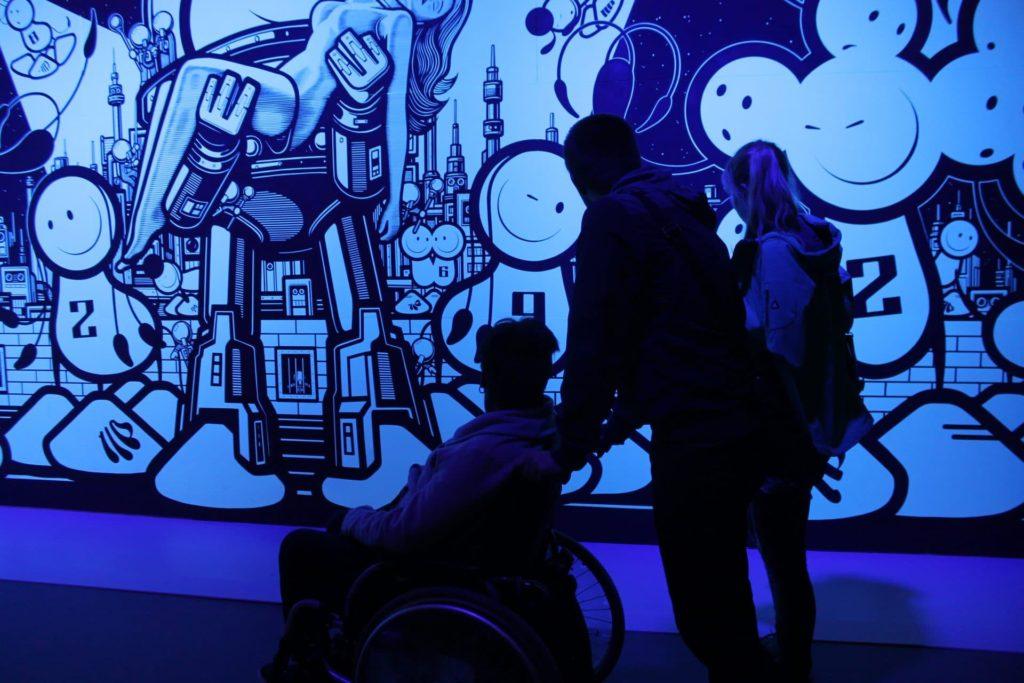 Ein Mitarbeiter der Alexander Thamm GmbH mit einem Bewohner der Pfennigparade bei der Magic Life Ausstellung.